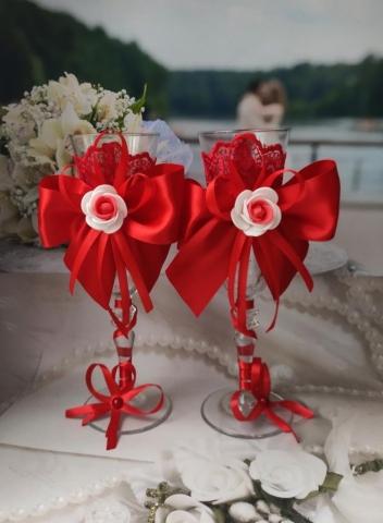 красные бокалы на свадьбу с бантами и розами